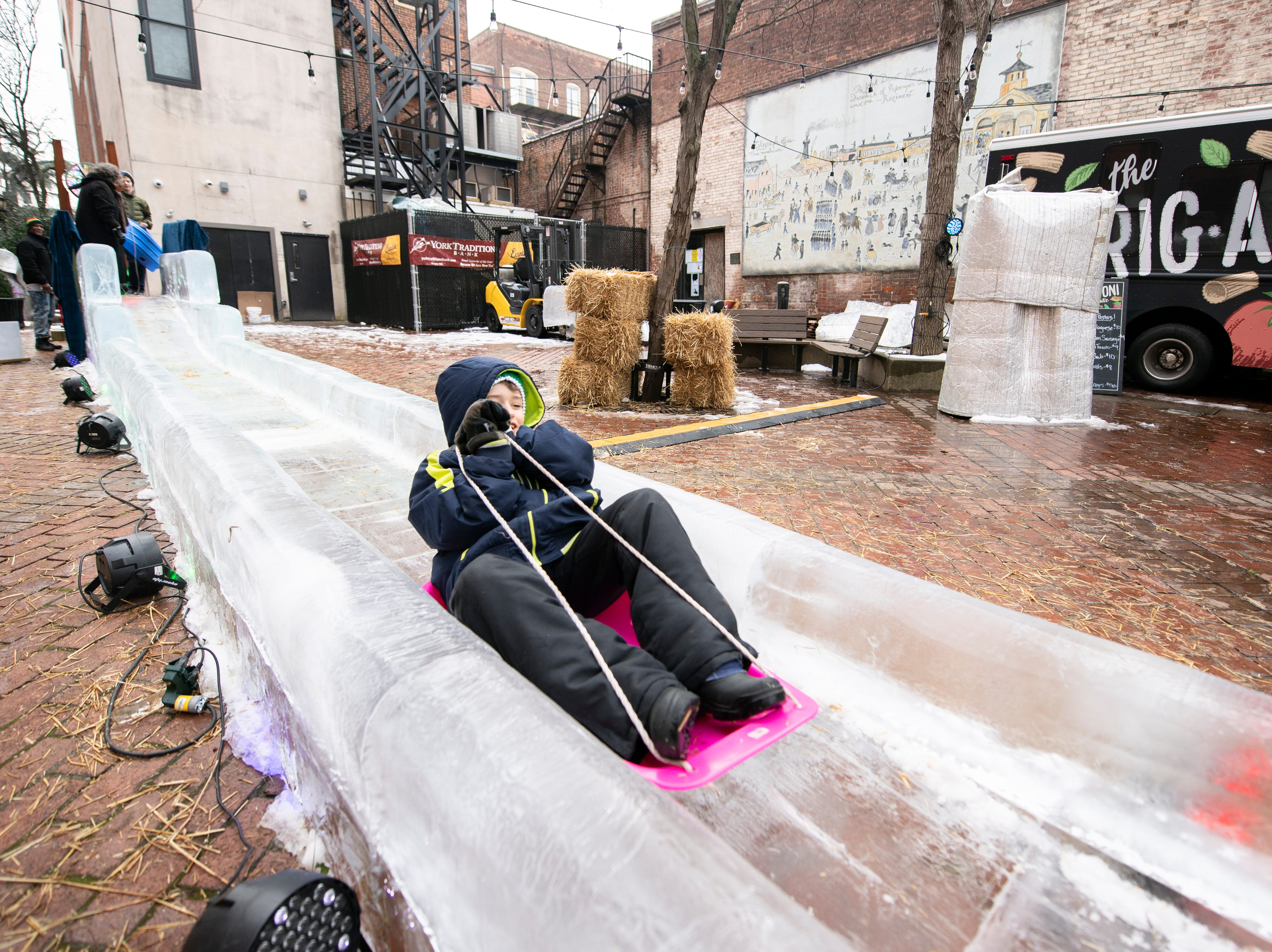 Brayden Arnold, 8, of East York, rides a sled down the 40-foot ice slide in Cherry Lane, downtown, Friday, Jan. 18, 2019. The FestivICE ice festival has interactive ice sculptures, an ice slide and more. The three-day event ends Saturday.