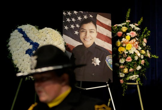 A photo of Davis Police Officer Natalie Corona is shown between wreaths before funeral services for Corona at the University of California, Davis, Friday, Jan. 18, 2019, in Davis, Calif. Corona was was shot and killed Jan. 10, responding to scene of a three-car crash in Davis.  Police say gunman Kevin Douglas Limbaugh, 48, not involved in the crash,  rode up on a bicycle and without warning, opened fire on Corona. (AP Photo/Rich Pedroncelli, pool)