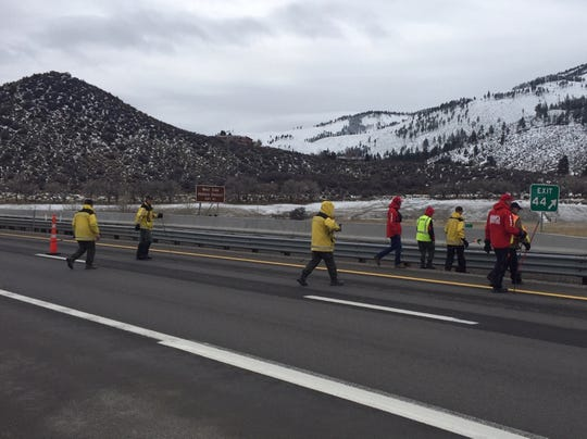 Volunteers for the Washoe County Sheriff's Office's Search and Rescue team walk through the I-580 corridor in search of any evidence linked to the murder of an elderly couple in south Reno.