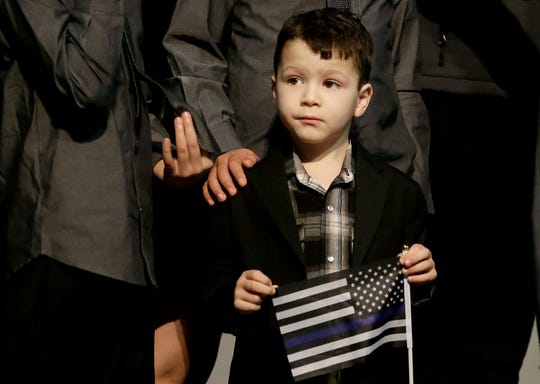 Mason Martinez holds up a flag before funeral services for his cousin, Davis Police Officer Natalie Corona, at the University of California, Davis, Friday, Jan. 18, 2019, in Davis, Calif.   Corona was was shot and killed Jan. 10, responding to scene of a three-car crash in Davis.  Police say gunman Kevin Douglas Limbaugh, 48, not involved in the crash,  rode up on a bicycle and without warning, opened fire on Corona.(AP Photo/Rich Pedroncelli, pool)