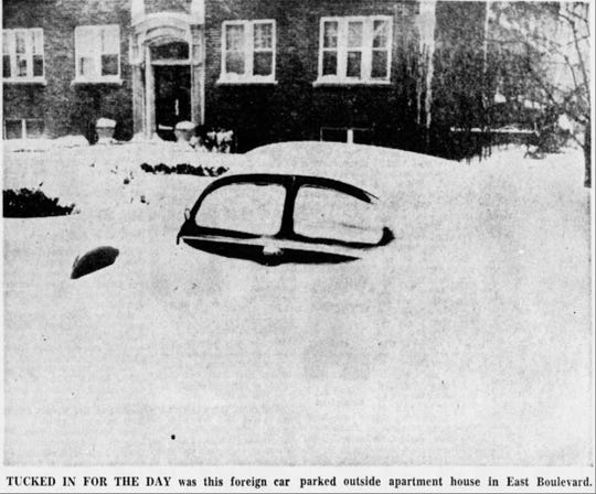 A car buried in snow on March 14, 1960 .