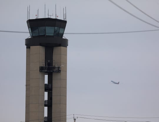 An airplane takes off from the Greater Rochester International Airport flying behind the Rochester Air Traffic Control Tower.