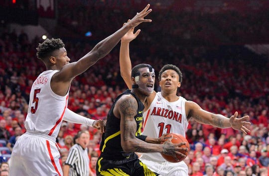 Jan 17, 2019; Tucson, AZ, USA; Oregon Ducks forward Kenny Wooten (14) prepares to shoot the ball as Arizona Wildcats guard Brandon Randolph (5) and forward Ira Lee (11) defend during the first half at McKale Center. Mandatory Credit: Casey Sapio-USA TODAY Sports