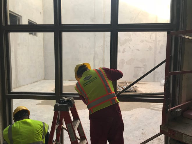 Workers from Cornerstone Construction install detention-grade glass in a pod at the new Tom Green County Jail. The new jail facility is designed to allow plenty of natural light in during the day.