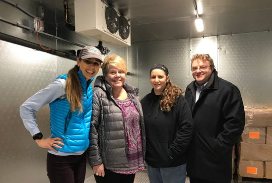 Lauren Smith, Lizabeth Kroll, Jodie Zajkowski and Patrick Boyle of the Sheboygan County Food Bank chill in the organization's new freezer.