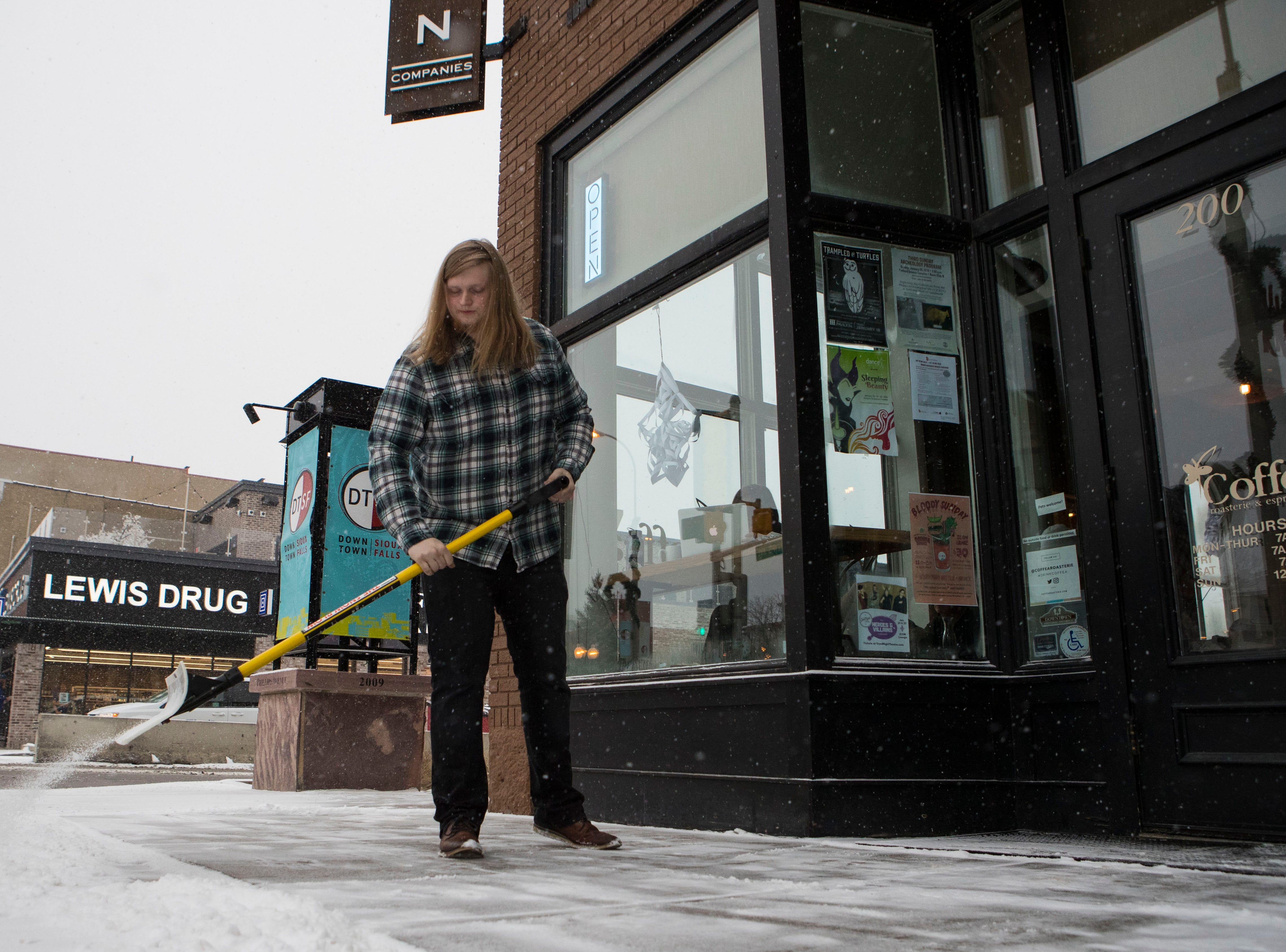 Doug Hair shovels snow outside of Coffea during a snow storm in Sioux Falls, S.D., Friday, Jan. 18, 2019.