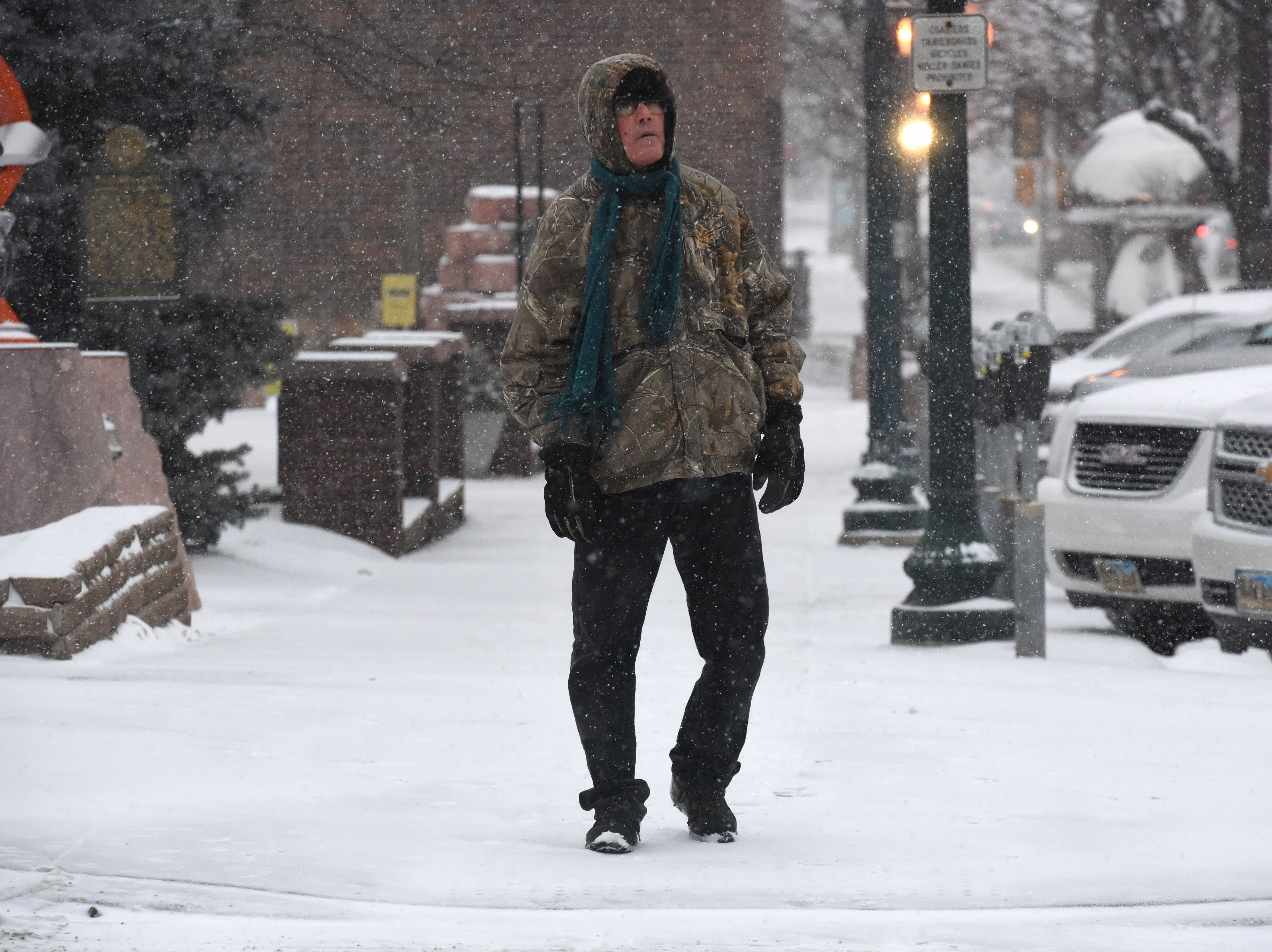 A man walks downtown during a snow storm in Sioux Falls, S.D., Friday, Jan. 18, 2019.