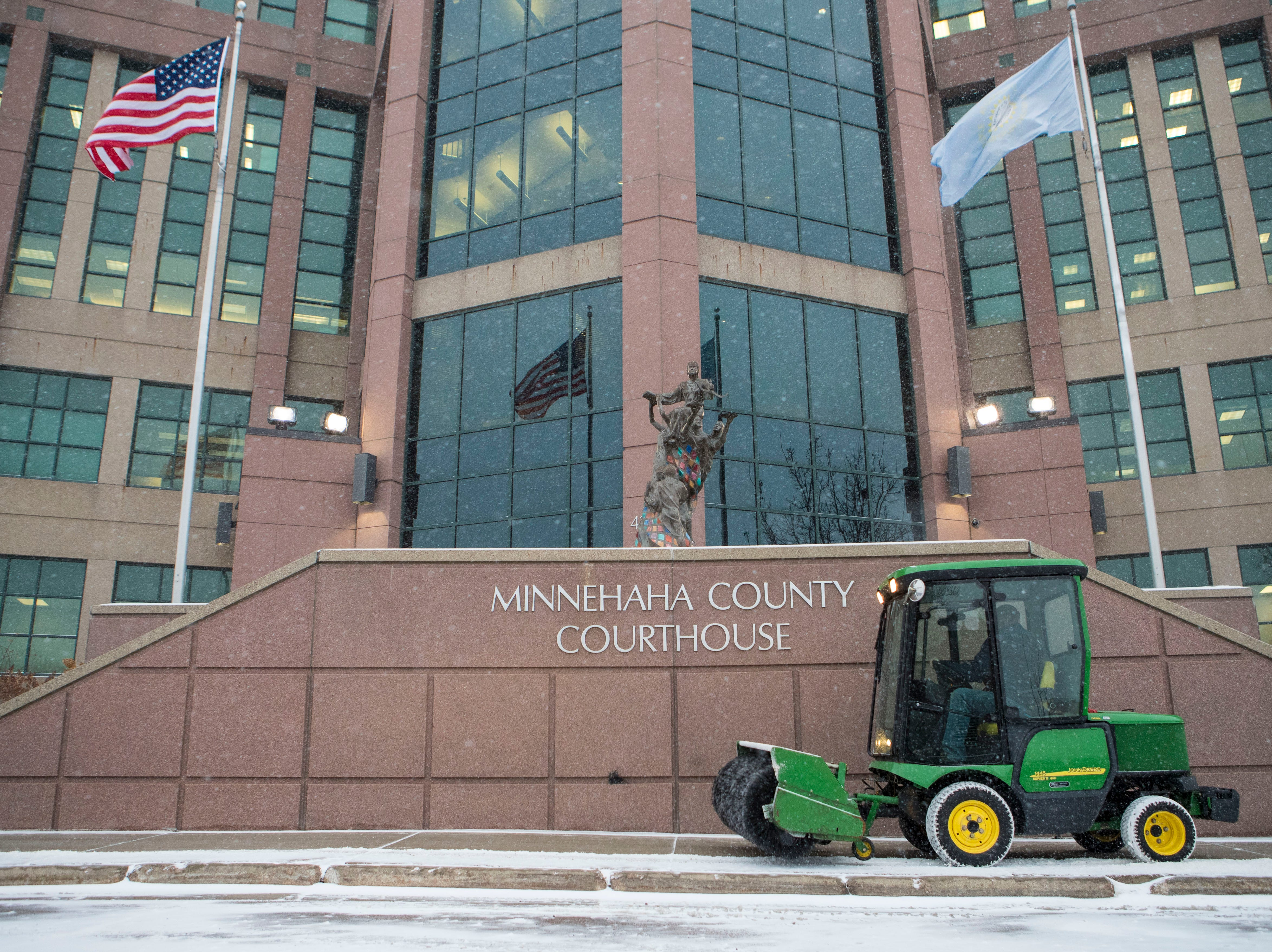 Man plows the Minnehaha County Courthouse sidewalk in Sioux Falls, S.D., Friday, Jan. 18, 2019.