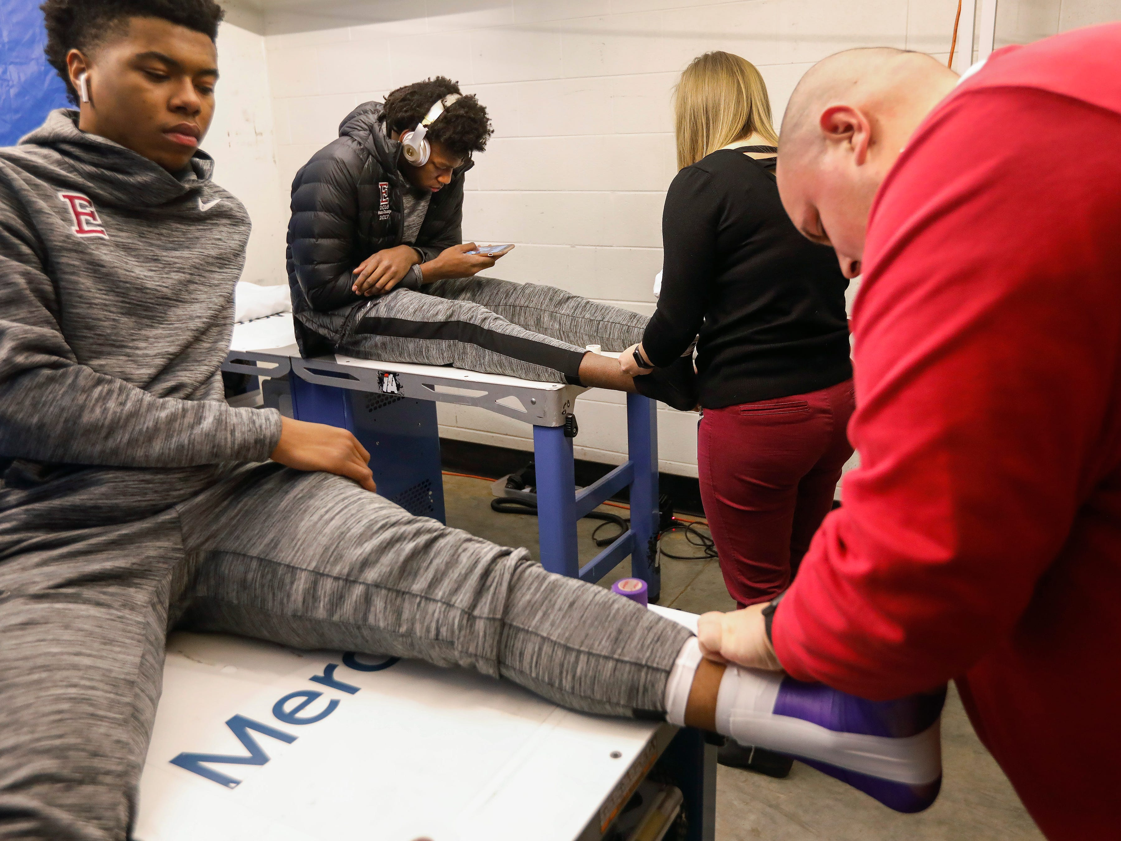 James Wiseman, center, of Memphis East High School, looks at his phone while getting taped up at JQH Arena for the Bass Pro Shops Tournament of Champions on Thursday, Jan. 17, 2019.