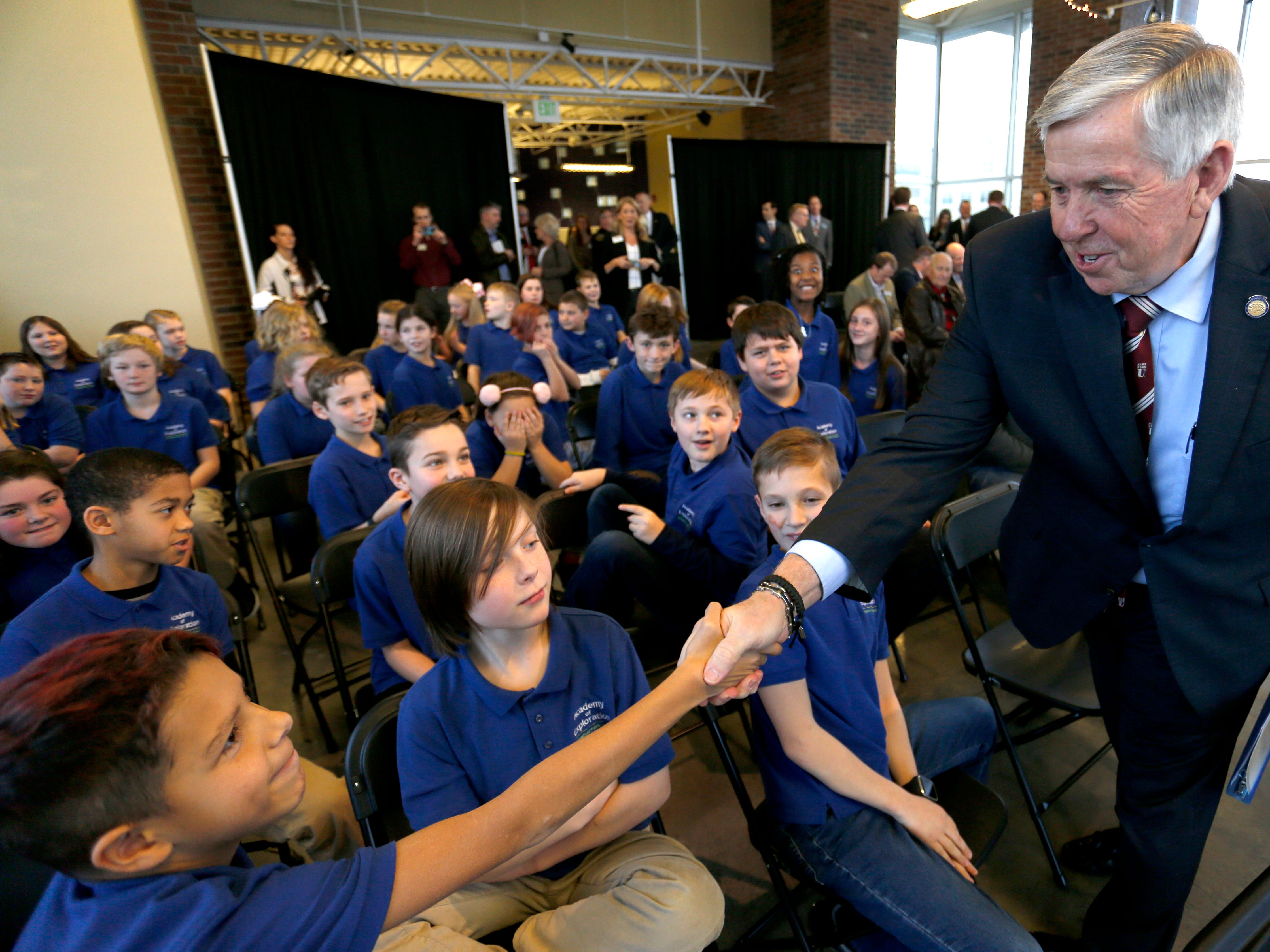 Gov. Mike Parson shakes hands with children from the Academy of Exploration at the Discovery Center on Friday, Jan. 18, 2019. Parson announced a grant of almost $474,000 from the Missouri Department of Economic Development to go toward STEM and opioid education.