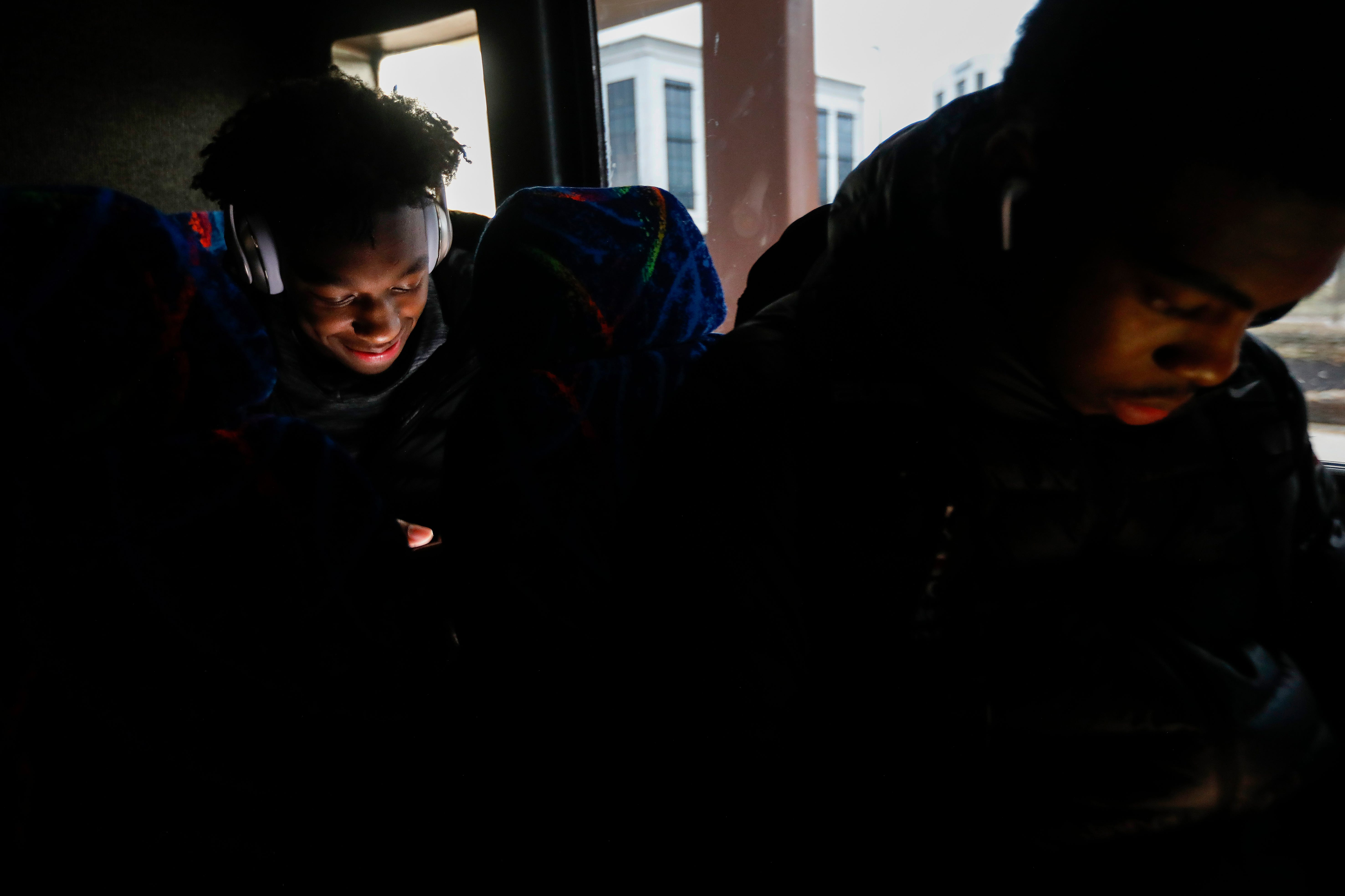 James Wiseman, left, of Memphis East High School, smiles as he looks at his phone while riding on the bus to JQH Arena for the Bass Pro Shops Tournament of Champions on Thursday, Jan. 17, 2019.