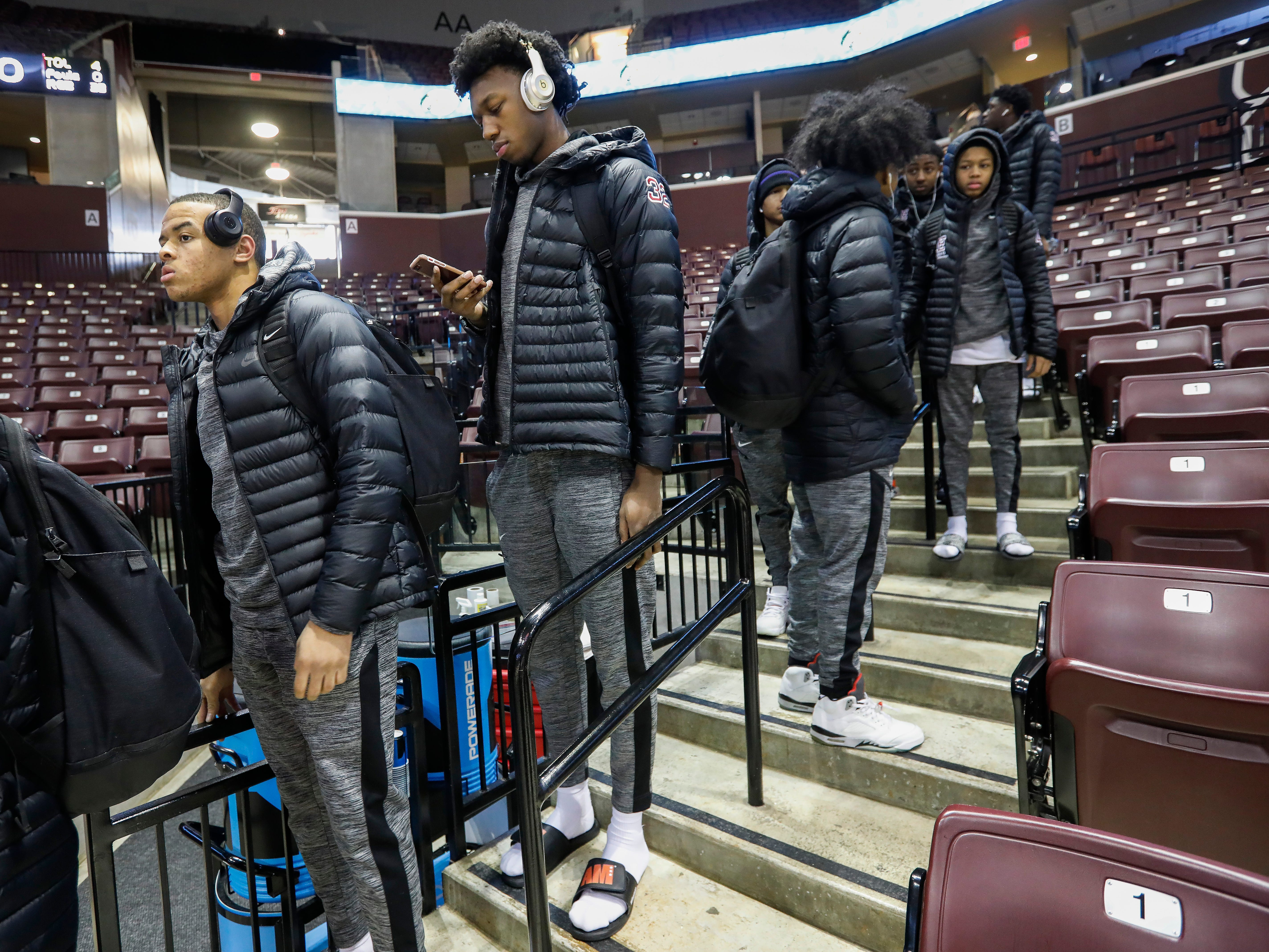 James Wiseman, center, of Memphis East High School, looks at his phone while waiting to go to the locker room at JQH Arena for the Bass Pro Shops Tournament of Champions on Thursday, Jan. 17, 2019.