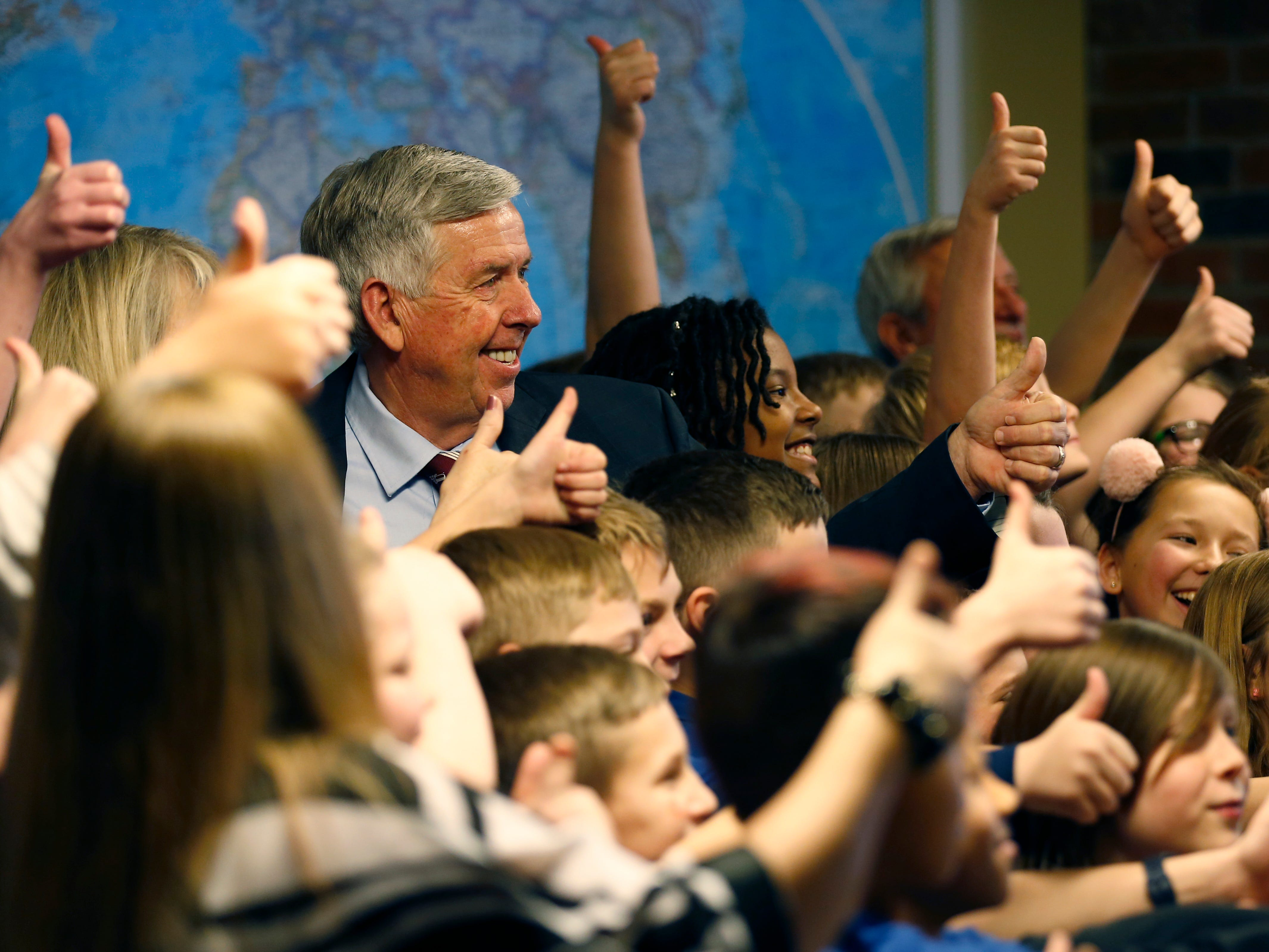 Gov. Mike Parson poses with a group of children from the Academy of Exploration at the Discovery Center on Friday, Jan. 18, 2019. Parson announced a grant of almost $474,000 from the Missouri Department of Economic Development to go toward STEM and opioid education.