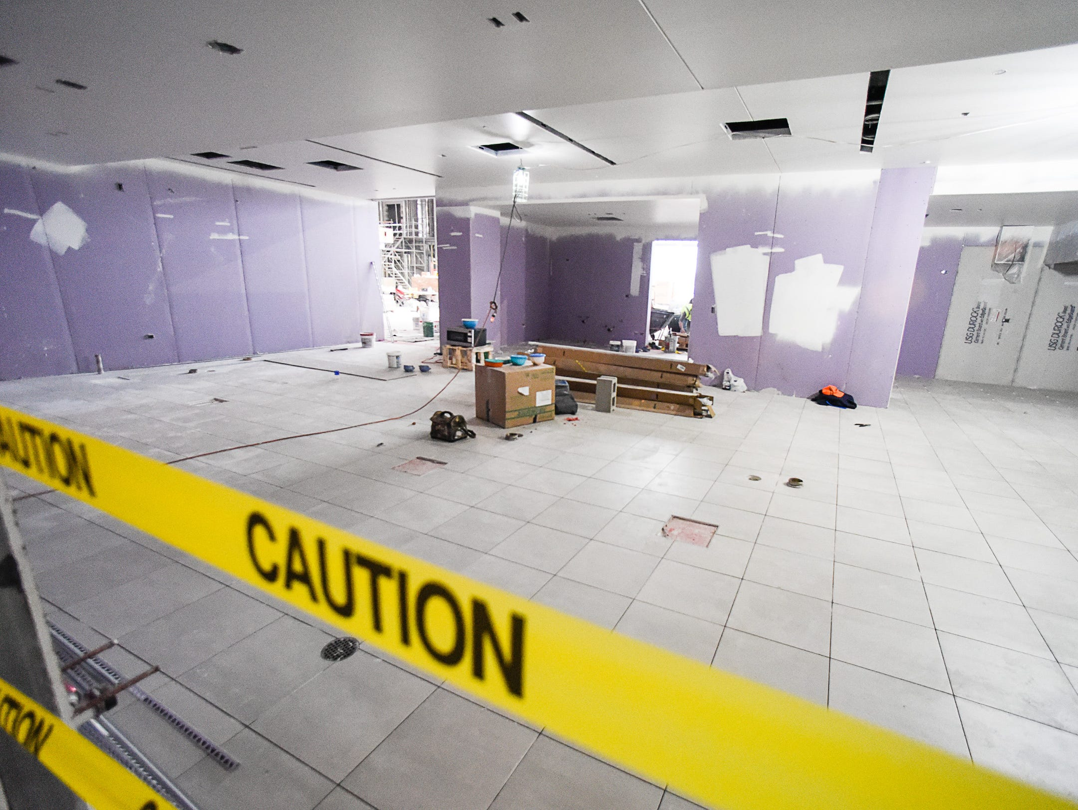 The floor tile is being put in Thursday, Jan. 17, in the food service area at the new Tech High School.