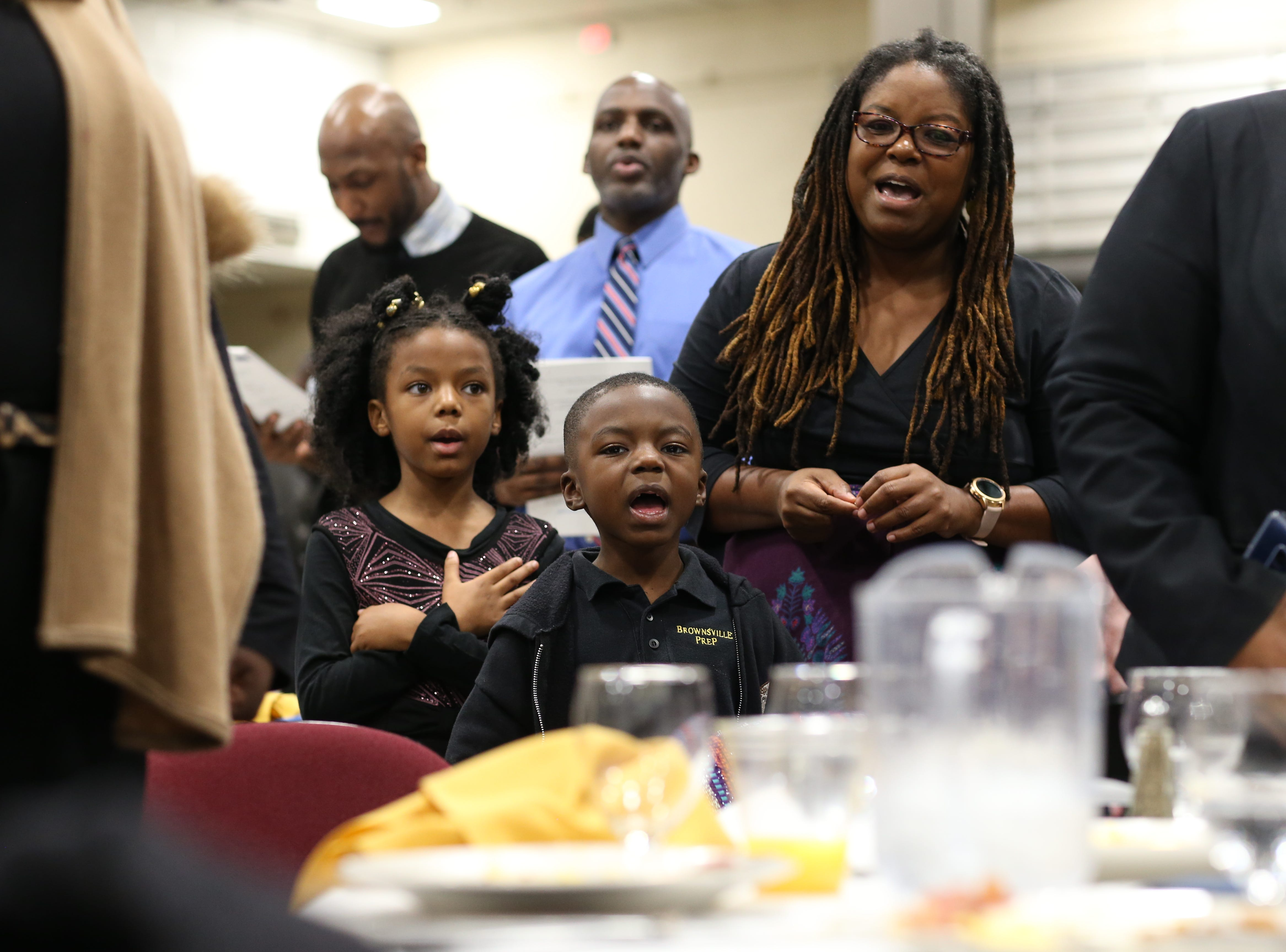 "Eddie Oliver II, 6, center, his sister Madison Oliver, 8 and his mother Andrew Oliver sing along to the Negro National Anthem ""Lift Every Voice and Sing"" during the Martin Luther King Jr. commemorative breakfast at Donald L. Tucker Civic Center Friday, Jan. 18, 2019."