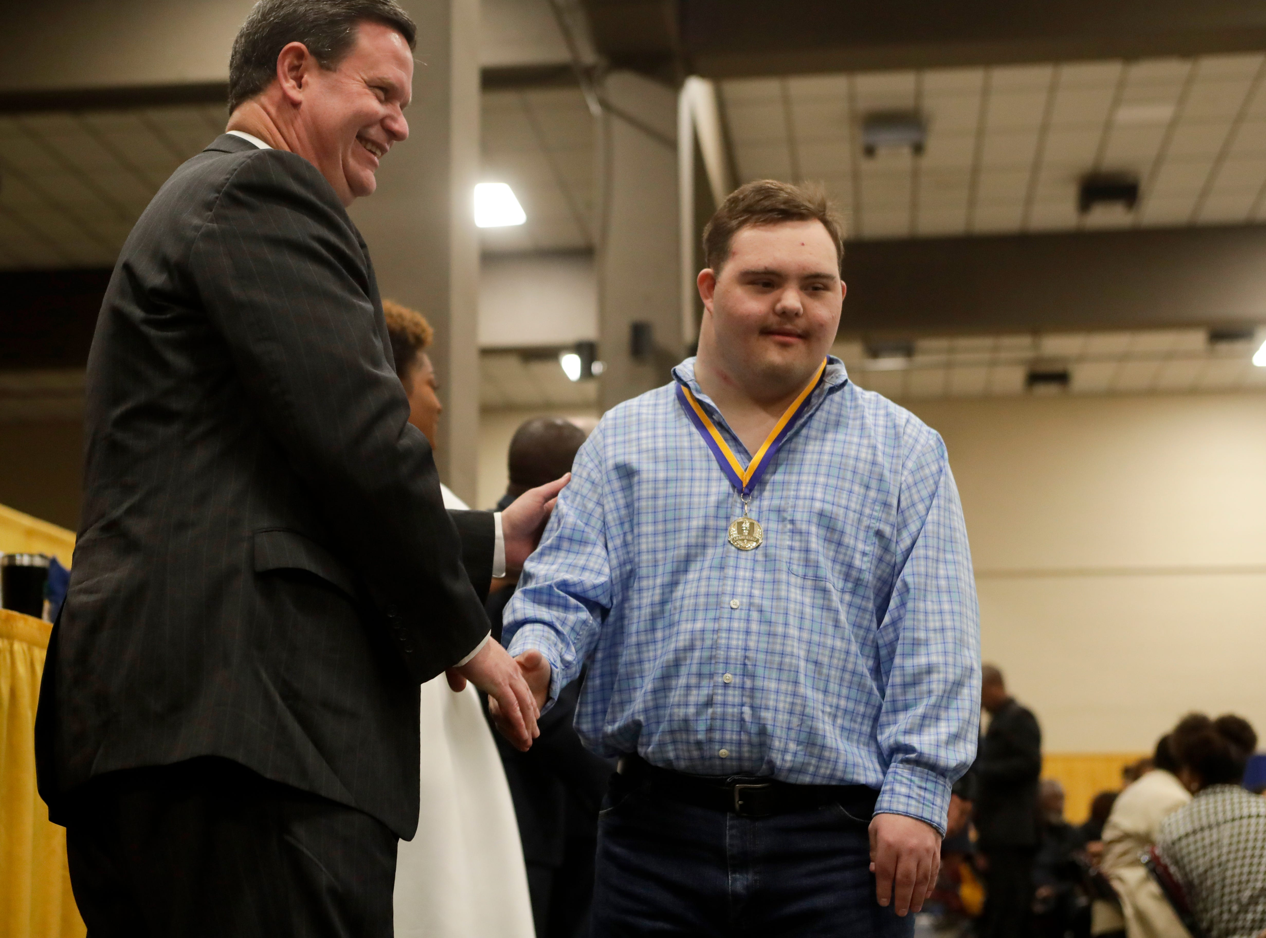 "Justin Dodson, 21, a Gretchen Everhart School student, shakes hands with Mayor John Dailey after receiving a medal at the Martin Luther King Jr. commemorative breakfast held at the Donald L. Tucker Civic Center Friday, Jan. 18, 2019. Leon County School students were given medals in recognition for being ""Dreamers and Doers."""