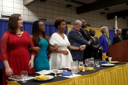 """Attendees lock arms and join in song singing """"We Shall Overcome"""" at the end of the Martin Luther King Jr. commemorative breakfast at Donald L. Tucker Civic Center Friday, Jan. 18, 2019."""