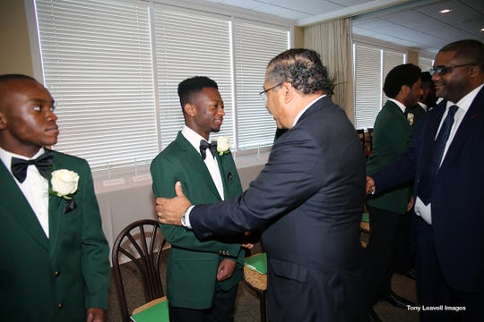 Former Mayor John Marks and Rev. Julius McAllister greet senior Zai'Vyon Price and 19 seniors at 9th Annual Green Coat Ceremony