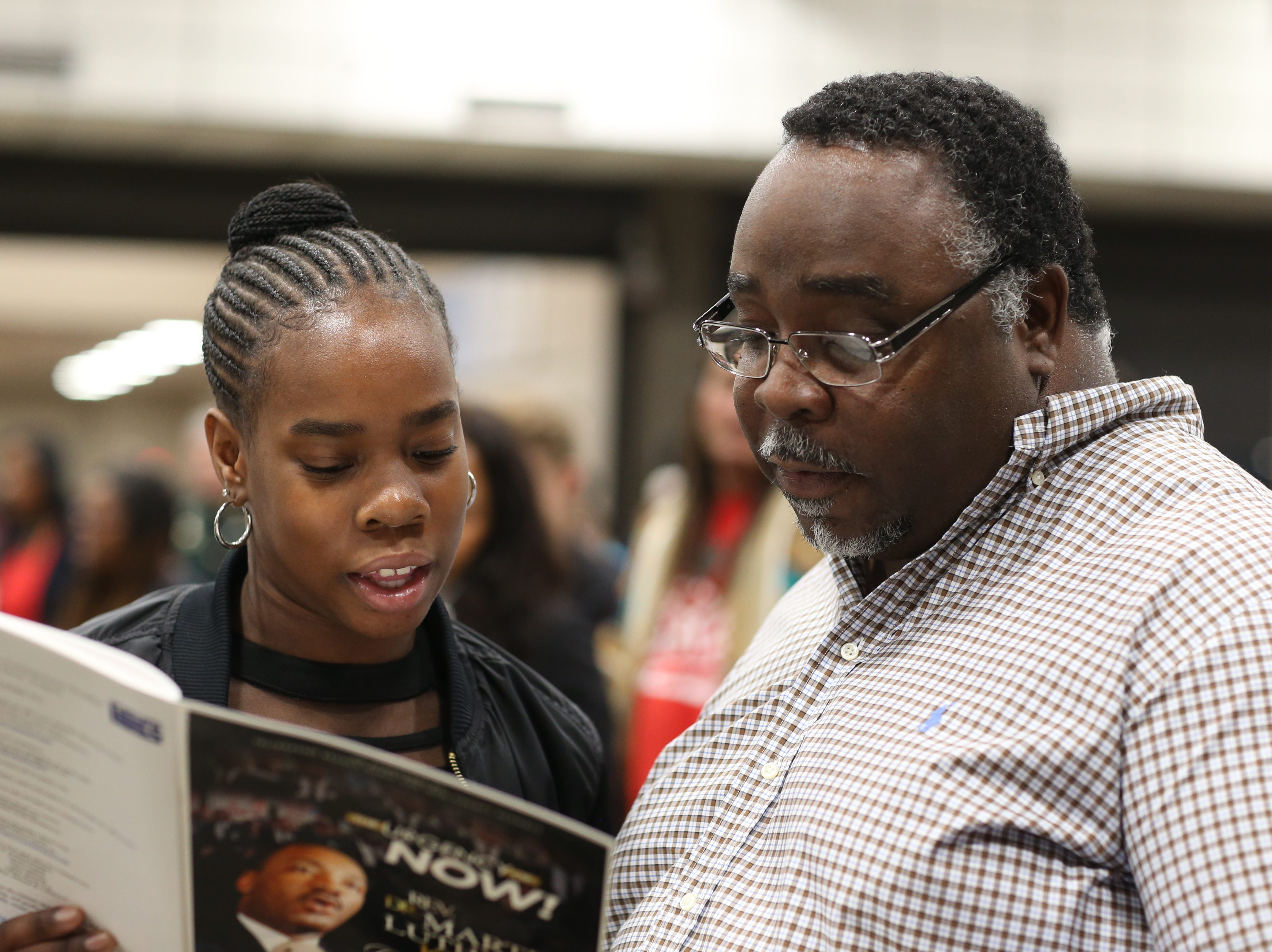 "Father and daughter Kirkland Ray and Kirsten Ray, 13, sing along to the Negro National Anthem ""Lift Every Voice and Sing"" during the Martin Luther King Jr. commemorative breakfast at Donald L. Tucker Civic Center Friday, Jan. 18, 2019."