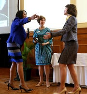 Dr. Marci Marano Beckis, right, is presented with a plaque by Nina Ashenafi-Richardson, left, and Nancy Miller, center, during the 2014 Trailblazer awards during Women's History Month.