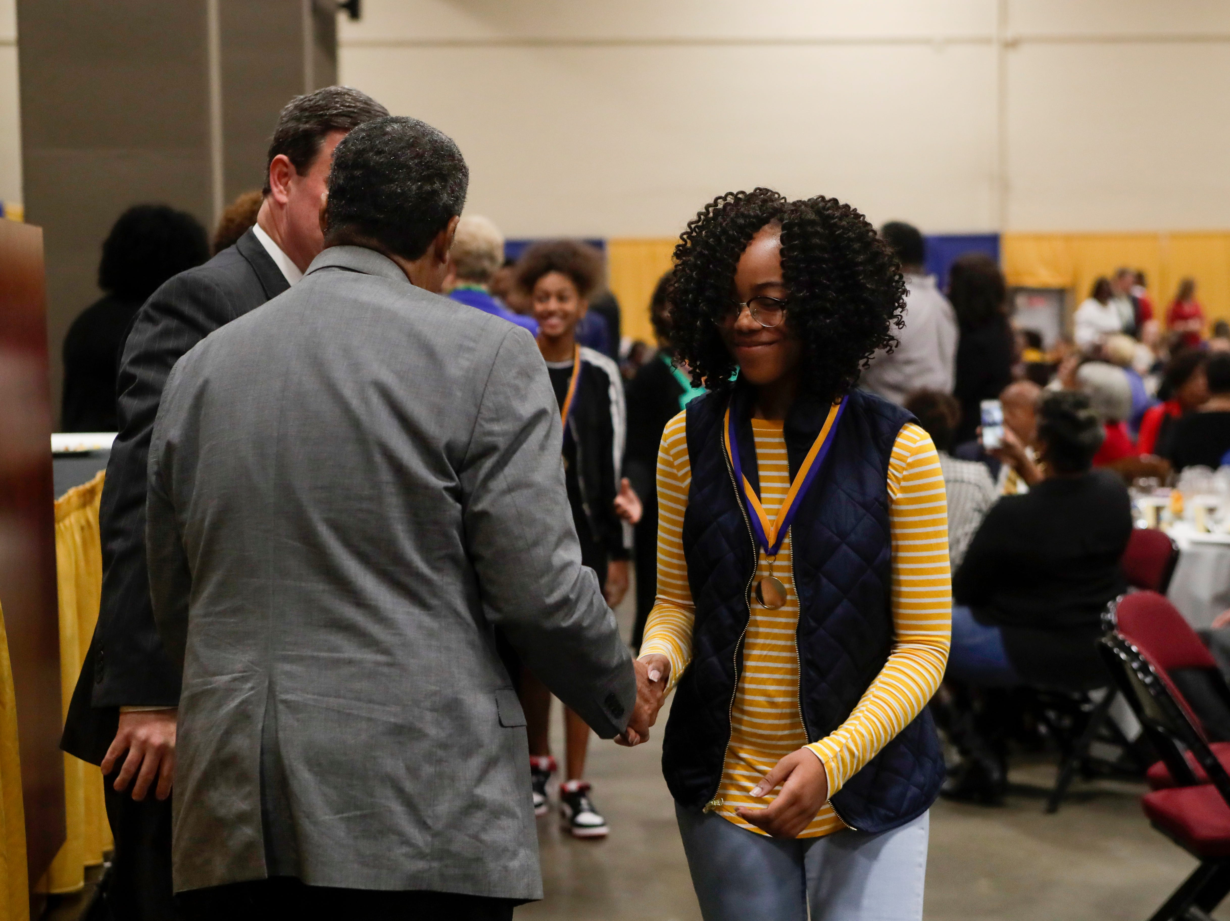 "Tamia Sanders, 14, of Fort Braden Middle School receives a medal and congratulations from area dignitaries at the Martin Luther King Jr. commemorative breakfast held at the Donald L. Tucker Civic Center Friday, Jan. 18, 2019. Leon County School students were given medals in recognition for being ""Dreamers and Doers."""