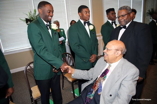 Dr. Jack Gant congratulates M'Kharis Lindsey and the other high school seniors at the Green Coat Ceremony Jan.13