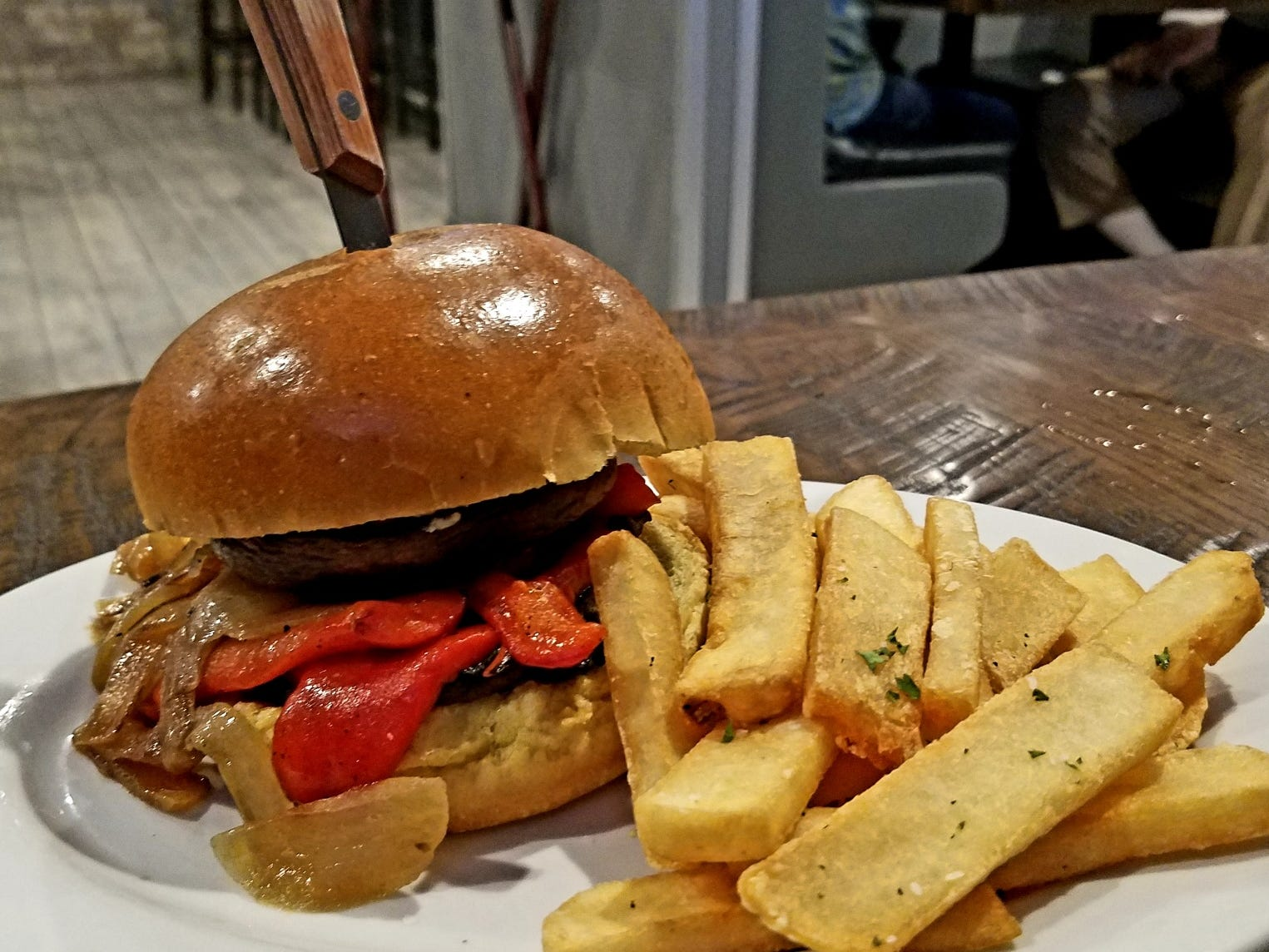 The farmers portobello burger is a brioche bun stuffed with a marinated portobello cap, sauteed onions, roasted red peppers and a smear of goat cheese served with  crispy seasoned steak fries.