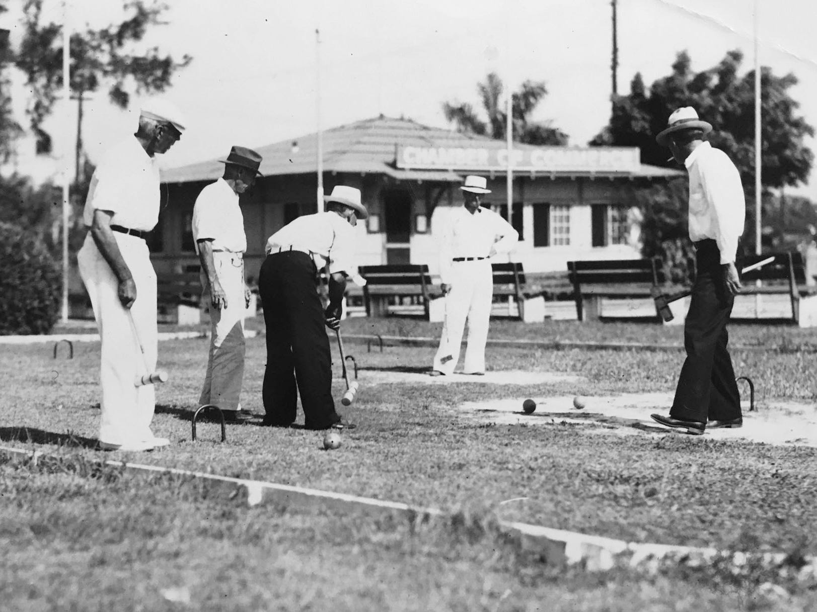 Until the 1960s, Pocahontas Park included a regulation croquet court, where players engaged in cutthroat variations of the more genteel lawn croquet. Their rules allowed competitors to bank shots off the concrete wall. This picture is believed to have been taken before 1953, before the old Chamber of Commerce building in the background was moved.