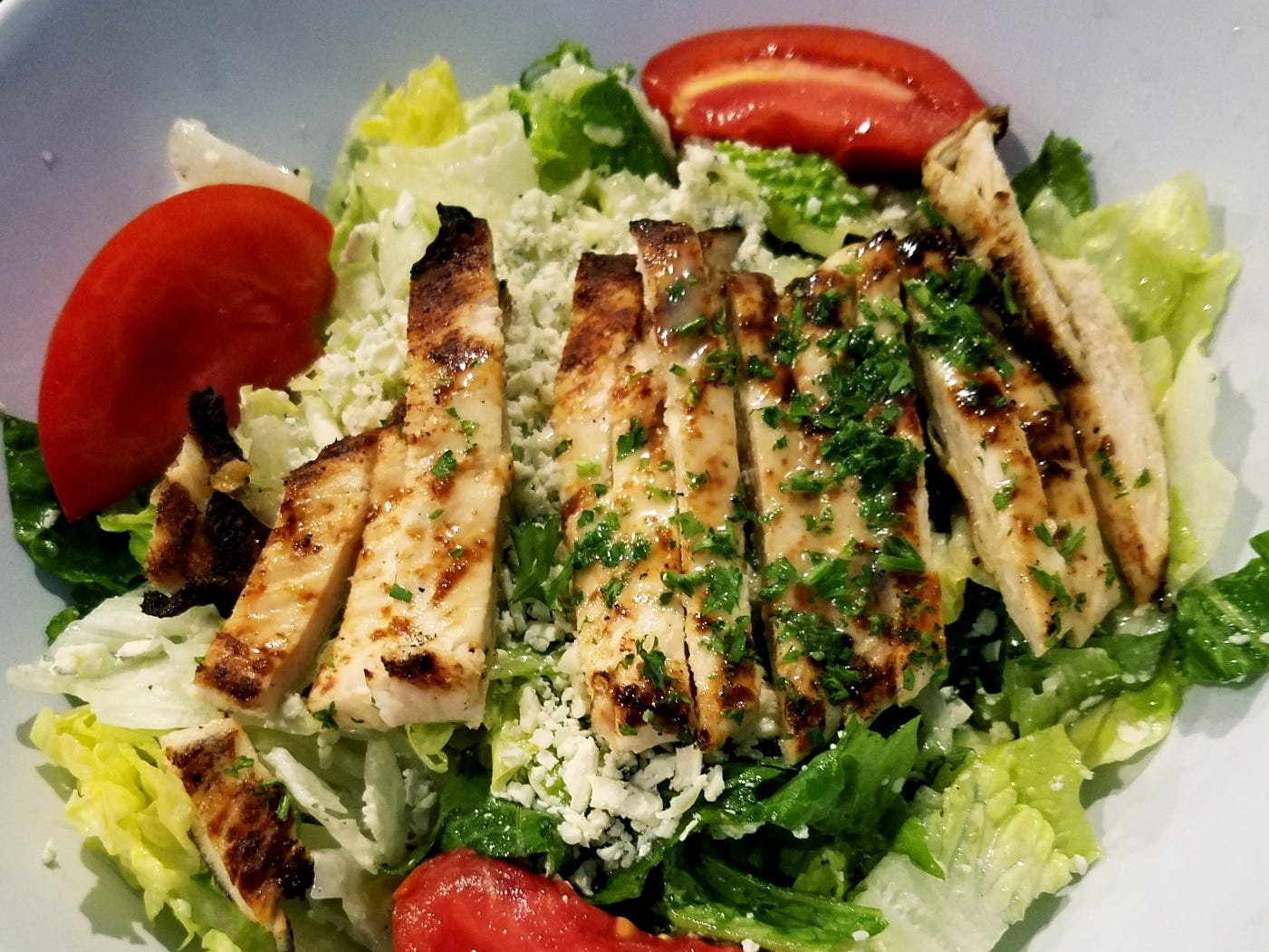 Manero's signature Gorgonzola salad romaine and iceberg lettuces tossed in housemade Italian dressing with tomato wedges and shredded Gorgonzola cheese. Seen here topped with gremolata seasoned chicken strips.