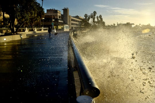 A large wave breaks over the concrete railing of the Ventura Promenade early Friday as the king tides break along the beach.