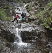 Participants in an earlier Sierra Club Wilderness Basics Course maneuver a water crossing.