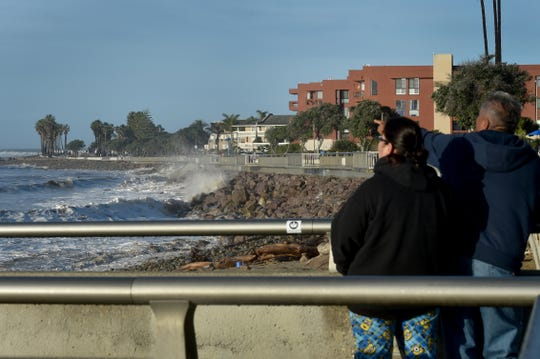 Ramon Ramirez and his wife, Caroline Moreno, watch large waves break along the Ventura Promenade on Friday during a dawn king tide.