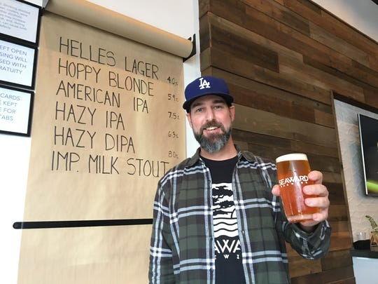 Jason Henrey, co-owner and head brewer at Seaward Brewery in Ventura, poses with a pint of American IPA in the taproom. The microbrewery is marking its grand opening this weekend.