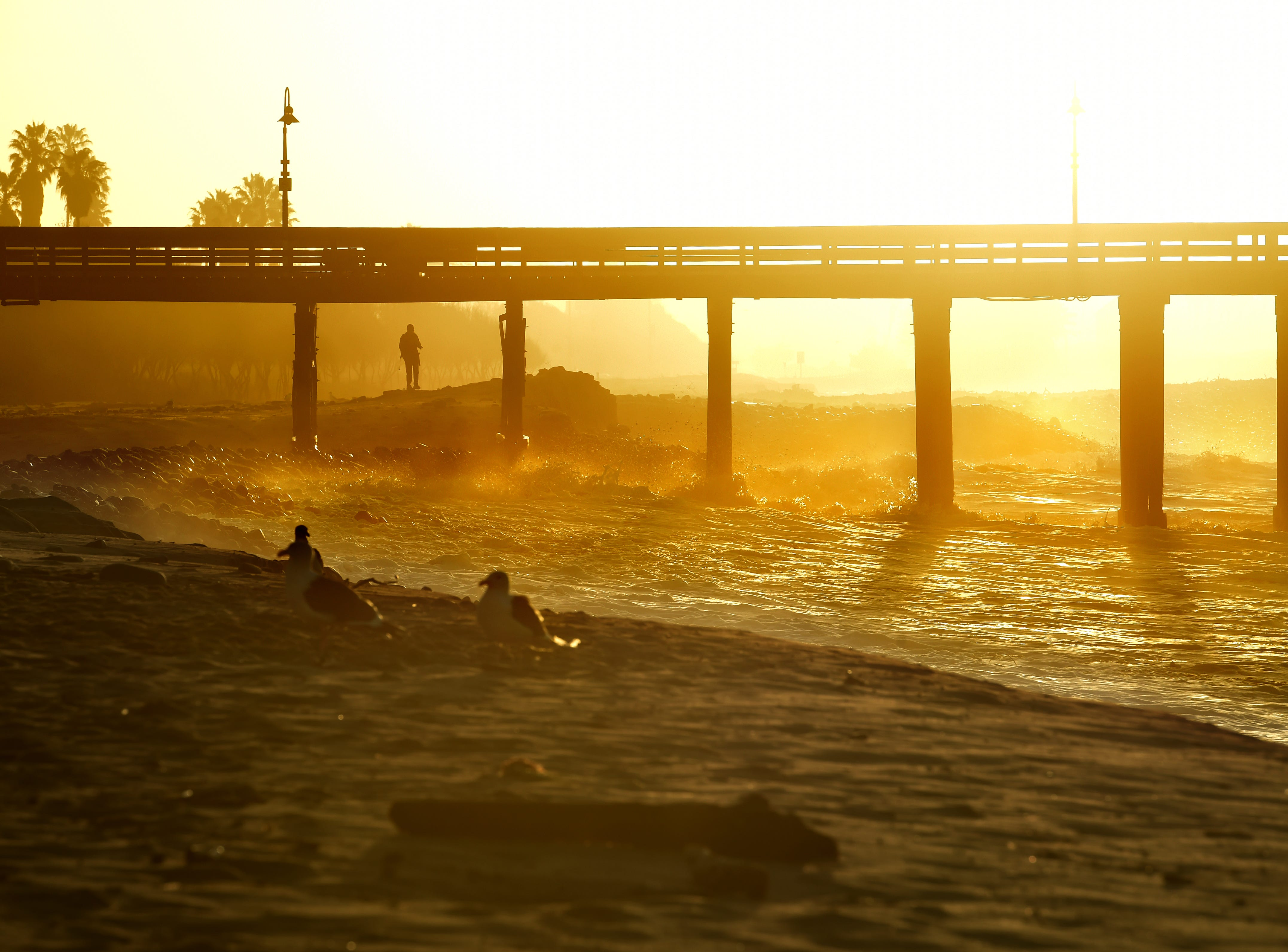 Morning visitors to the Ventura pier watch as the king tide sends large waves onto the shore early Friday.