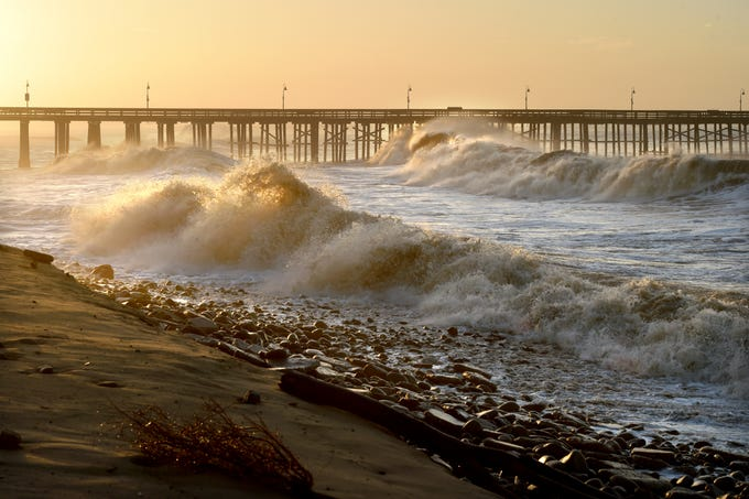 Large waves touch the top of the Ventura pier on Friday during the king tides on Ventura Beach.