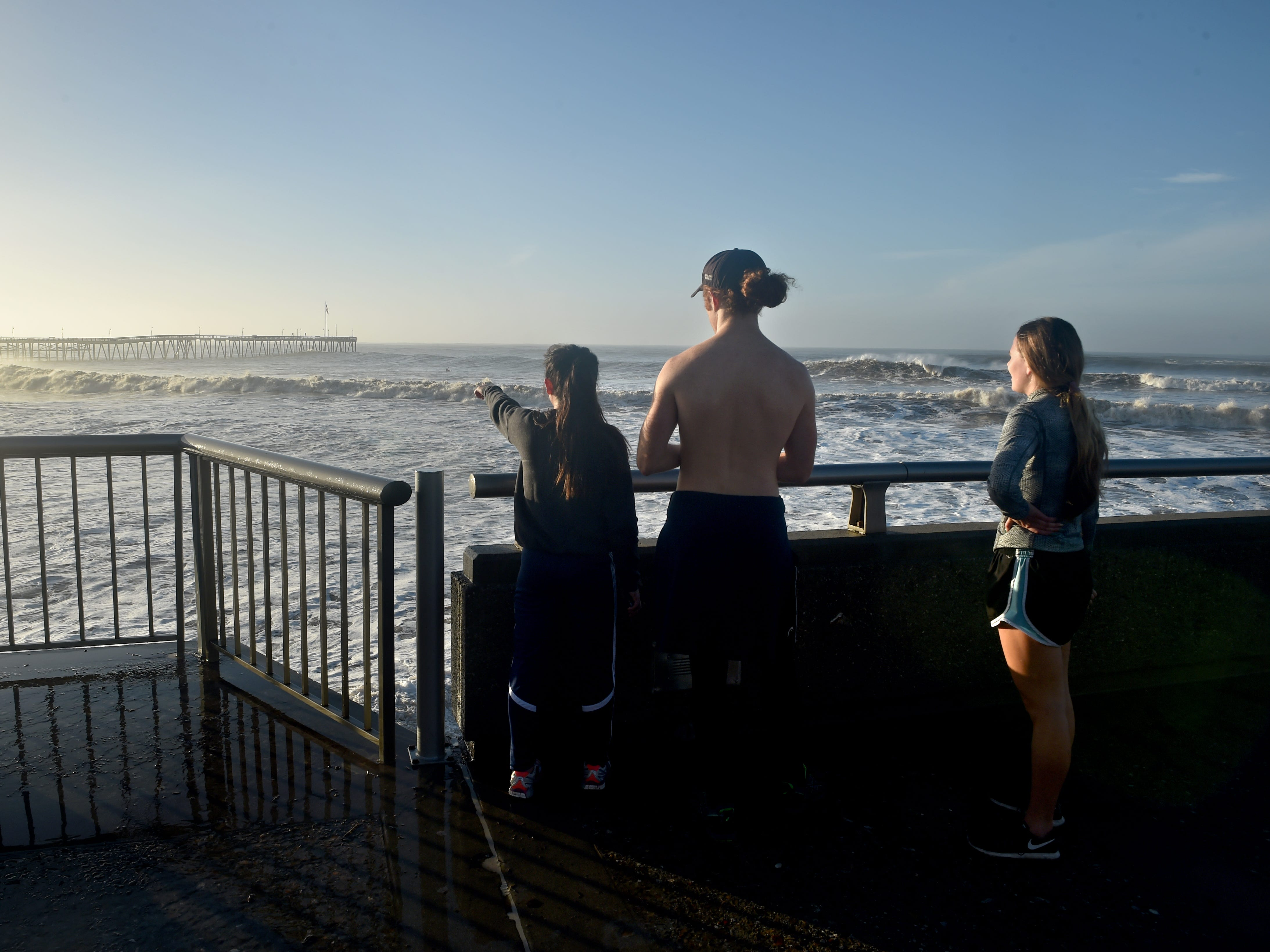 Friends Jamie Block, Travis Chamness and Cara Morrow (from left) watch large waves touch the top of the Ventura Pier on Friday during a dawn king tide.