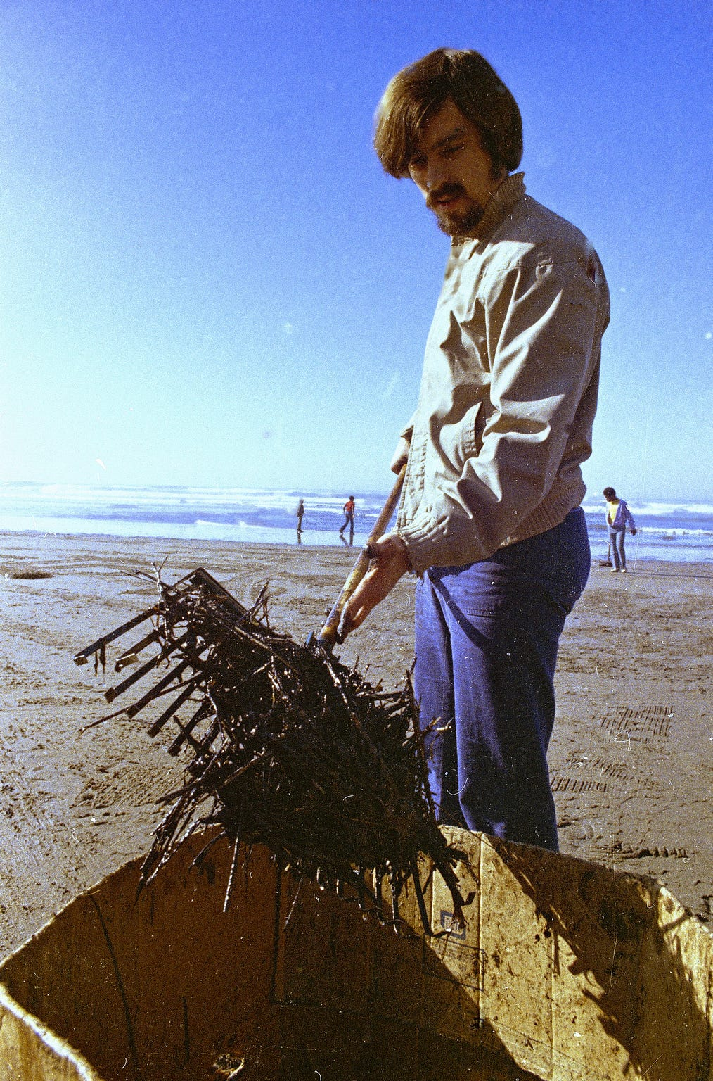 A workman using a pitchfork helps during the cleanup of oil-soaked straw from the beach at Santa Barbara Harbor in California on Feb. 7, 1969.  The oil, leaking from an off-shore well for over a week, covered local beaches and threatened many Southern California shoreline areas.  (AP Photo)