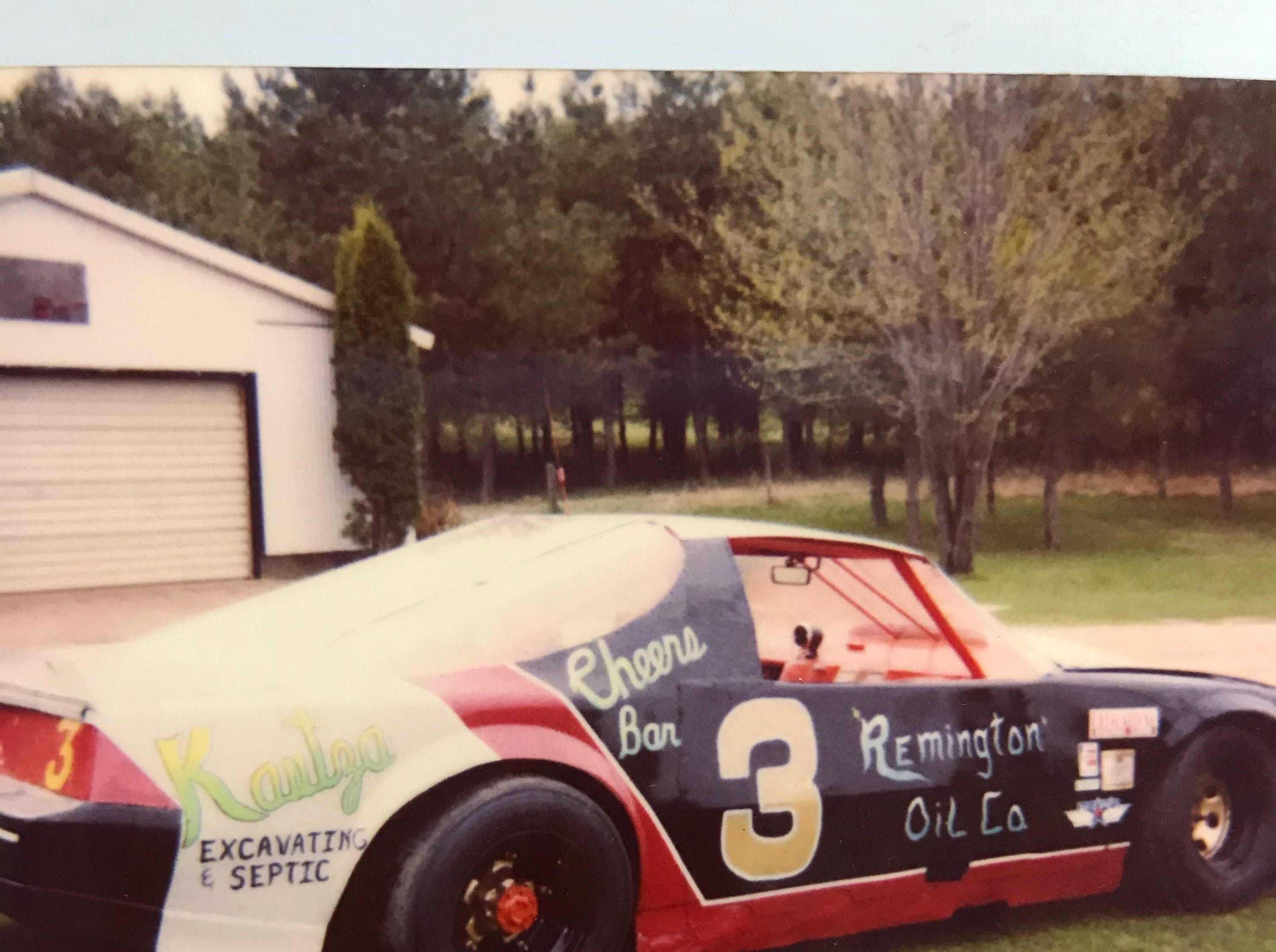 """An old car with """"Cheers Bar"""" on it."""