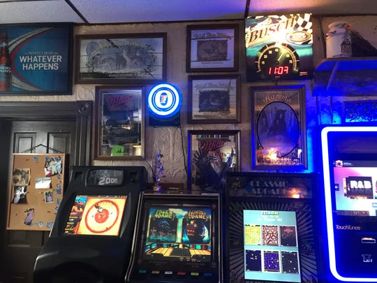 The walls at Cheers bar are plastered with various beer signs and lined with arcade games.