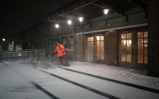 Metro-North employee Vito Sgaramella blows snow from the sidewalk at the Yonkers train station after a light dusting of snow on Jan. 18, 2019.
