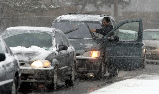 -  A motorist reaches for his still-moving windshield wipers as he tries to dislodge the ice cakes that formed while driving in Yonkers