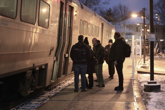 Commuters board an NJ Transit train at the Nanuet train station as snow coats the grassy areas, Friday, Jan. 18, 2019.
