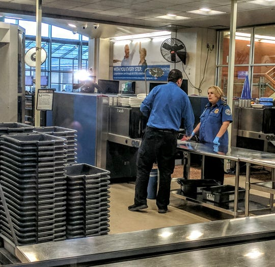 A TSA worker screens an air traveler on Jan. 18, 2018 at Westchester County Airport.