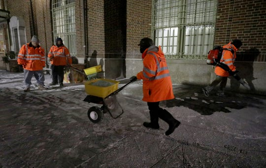 Metro-North employees blow snow from the sidewalks and put down a layer of salt at the Yonkers train station after a light dusting of snow on Jan. 18, 2019.