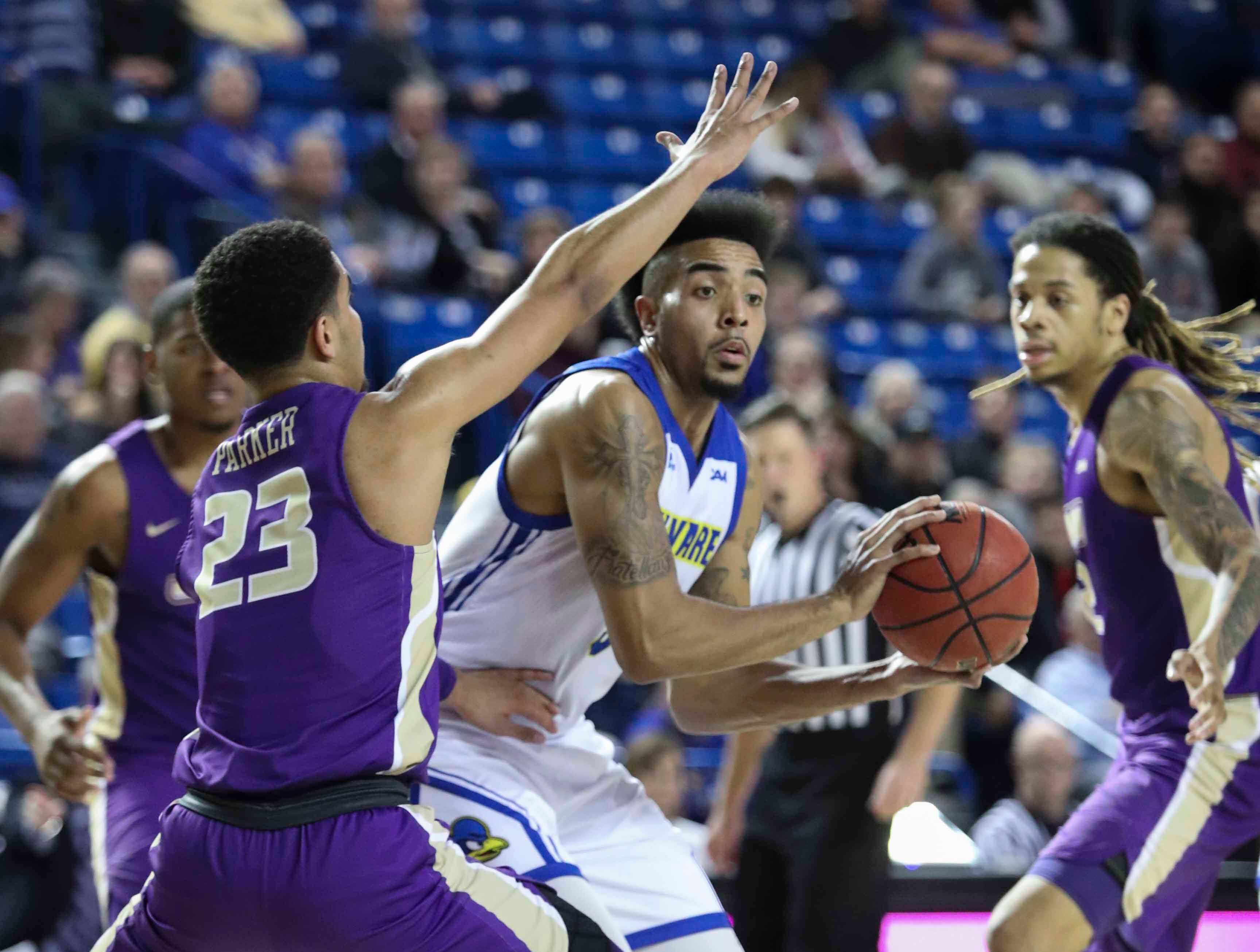 Delaware's Eric Carter (center) looks past James Madison's Deshon Parker in the second half of the Blue Hens' 76-69 win at the Bob Carpenter Center Thursday.