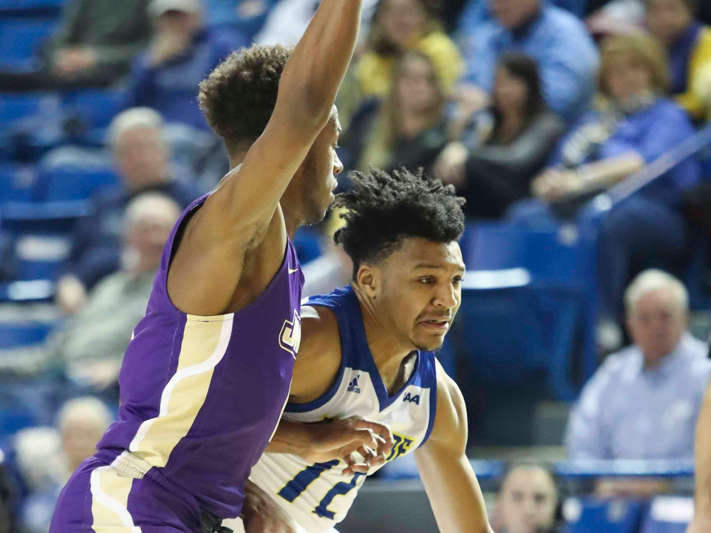 Delaware's Ithiel Horton drives as James Madison's Matt Lewis defends in the first half at the Bob Carpenter Center Thursday.