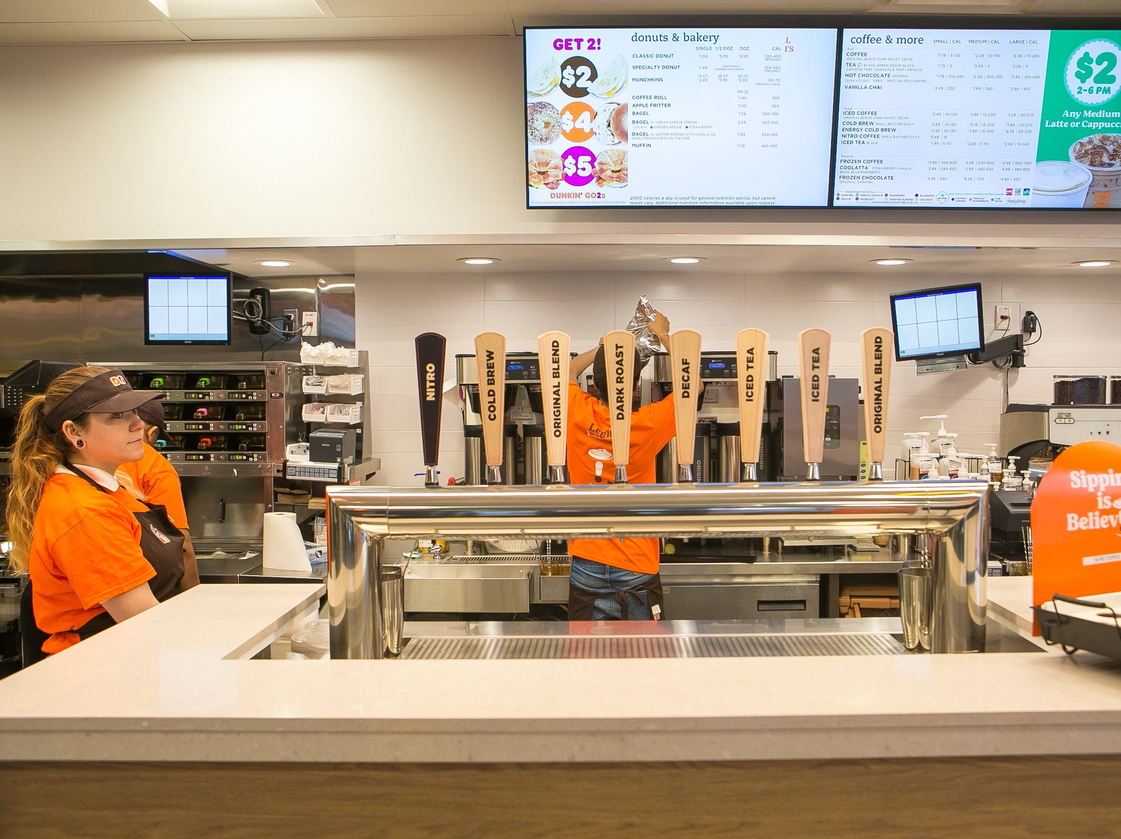 Ashley Keaton stands next to the new tap area that serves cold drinks. The Delaware store is one of about 60 new and remodeled Dunkin' restaurants with new designs and the new Dunkin' brand name.