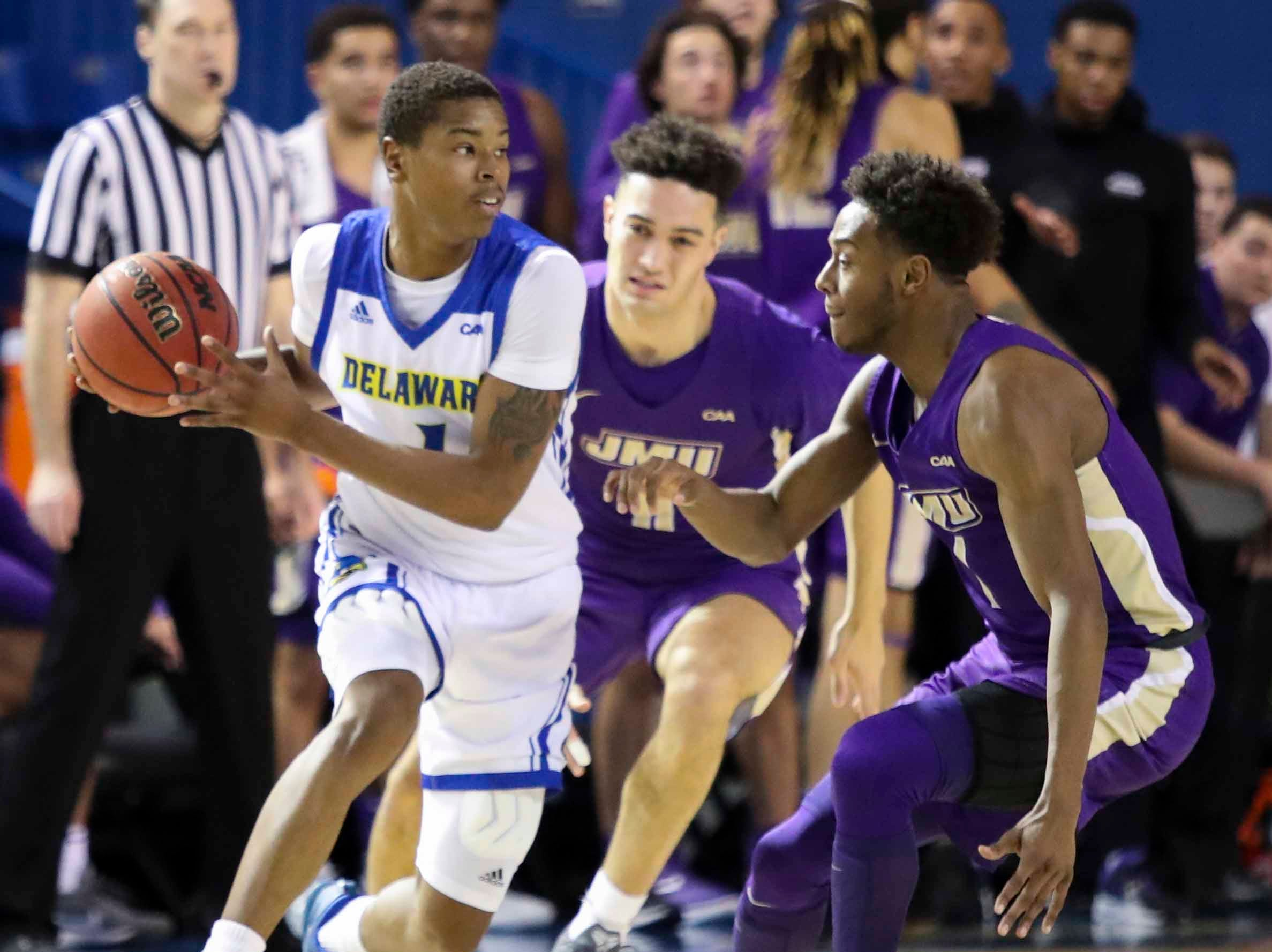 Delaware's Kevin Anderson works against James Madison's Zach Jacobs (center) and Matt Lewis in the first half at the Bob Carpenter Center Thursday.
