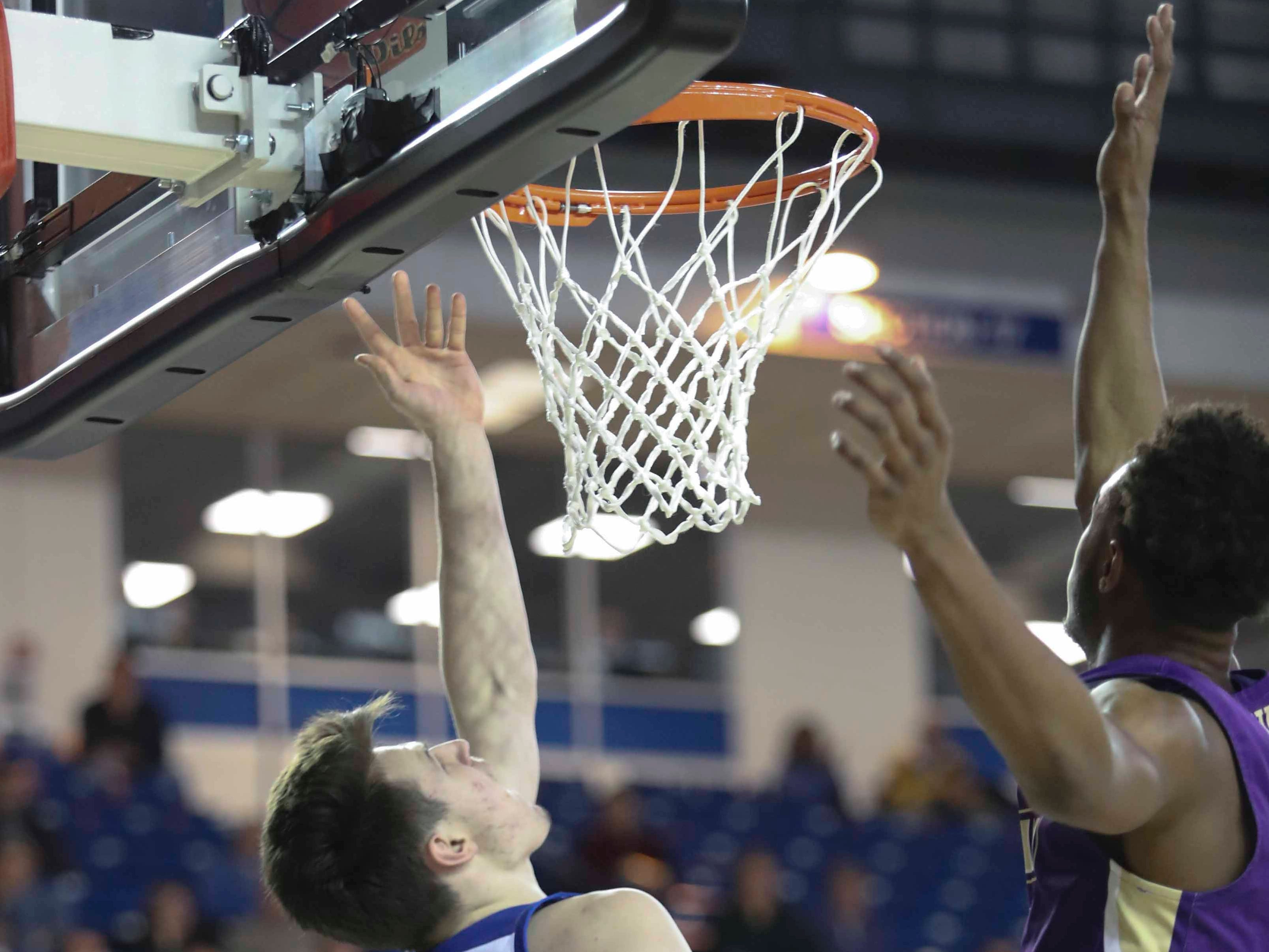 Delaware's Matt Veretto puts up a shot underneath the hoop in the second half of the Blue Hens' 76-69 win at the Bob Carpenter Center Thursday.