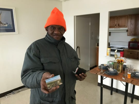Jessie Johnson displays his electronic benefit card, on which he receives food stamp money each month. It's the only income aside from a state assistance check the retiree has.